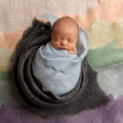 baby in blue blanket with rainbow background submitted as a fertility testimonial | Reproductive Science Center of the San Francisco Bay Area