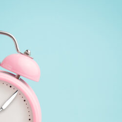 Pink alarm clock with fork and knife for hands for intermittent fasting | Reproductive Science Center of the SF Bay Area