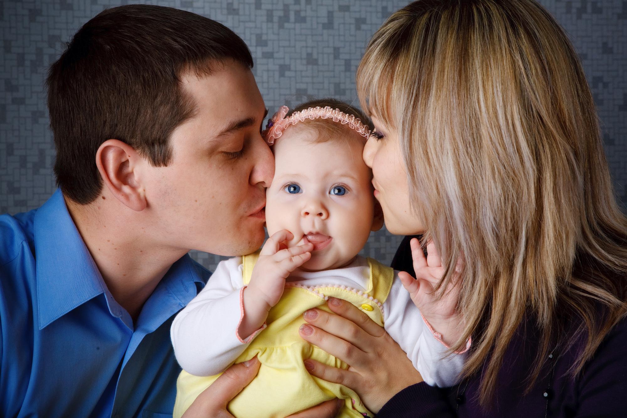 Spanish couple kissing cheeks of baby they conceived through IVF | Los Expertos en Fertilidad desde hace casi 30 años en el área de la bahía | RSC Bay Area